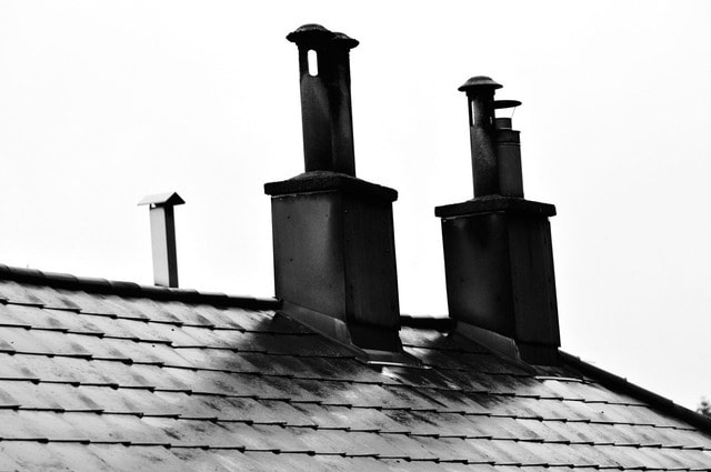 roof flashing on a shingle roof around two chimneys